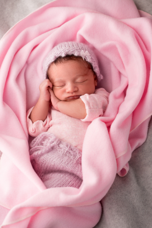 A newborn baby girl asleep, wrapped in a pink blanket and wearing a hat.