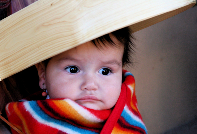 A baby girl with earrings is wrapped in a striped blanket.