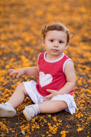 A toddler girl in Argentina with a heart on her dress, sitting on the ground with fallen orange leaves around her.