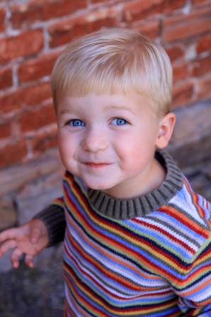 A toddler boy with blond hair and blue eyes, wearing a striped sweater, looking up and smiling.