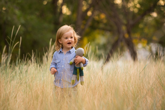 A toddler boy stands in a field, holding a stuffed animal and smiling.