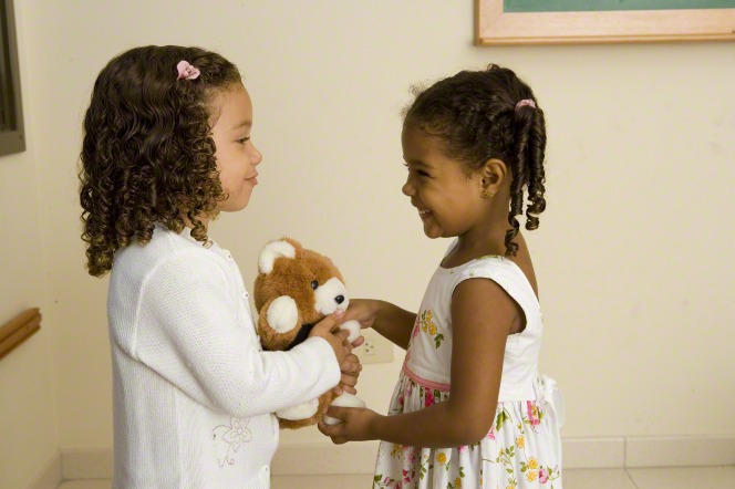 Two toddler girls in dresses standing and holding a teddy bear.
