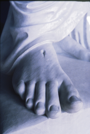 A close-up photograph of the foot of a white statue of Jesus Christ, showing the nail print and the hems of Christ's robes.