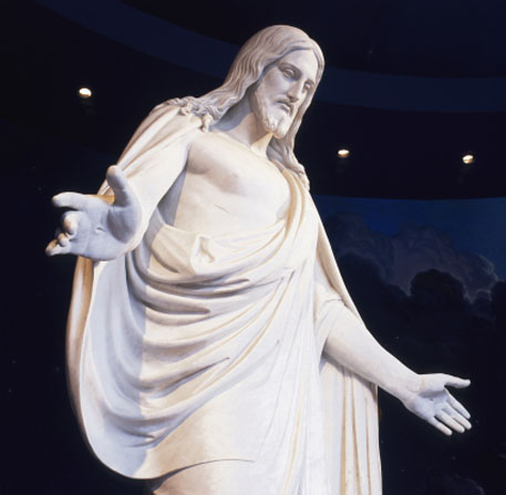 A white statue of Jesus Christ with arms outstretched, surrounded by a mural of blue sky.