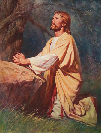 Christ in yellow and white robes, kneeling in the grass next to a large rock, with His hands clasped, looking upward.