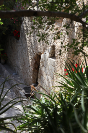A view of the entrance to the Garden Tomb in Jerusalem, seen through nearby green plants and the branch of an overhanging tree.