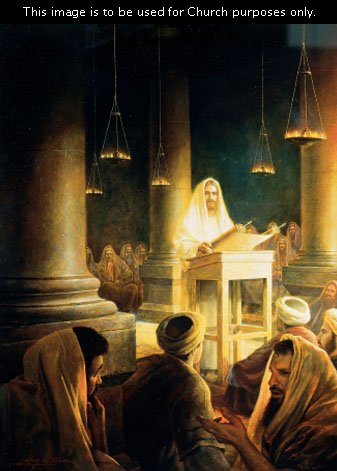 Jesus Christ in white robes, standing at the front of a congregation in the temple in Jerusalem, reading from a large scroll.