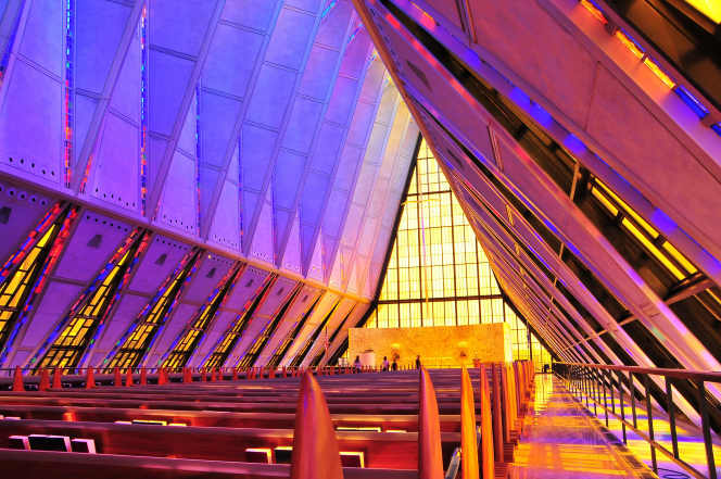 Rows of benches surrounded by stained-glass windows on each side inside a chapel at the Air Force Academy.