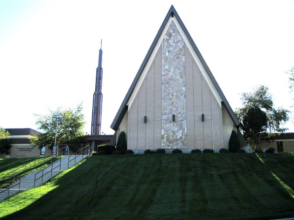 A front view of a chapel in Bountiful, Utah, in an A-shape with a steeple in the back and a green, grassy hill leading up to the chapel.
