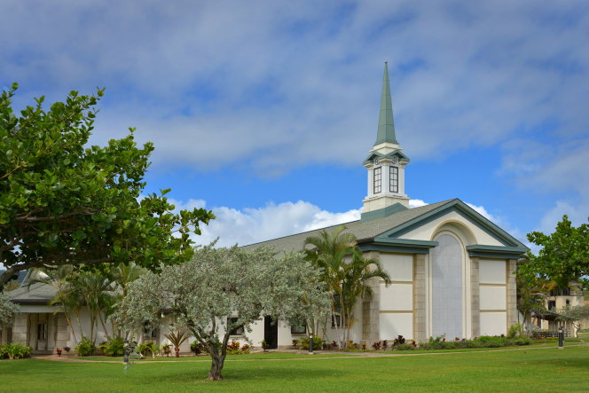 A green lawn and trees in front of a tan chapel with a steeple rising into the blue sky with clouds at BYU–Hawaii.