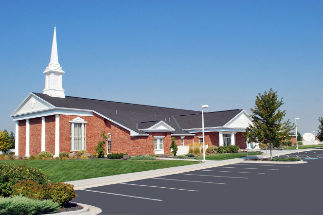 A side view of a parking lot and a red-brick chapel with a white steeple and a clear blue sky overhead in Caldwell, Idaho.