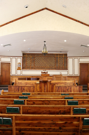 A view from the back of a chapel with rows of wooden benches and hymnbooks leading to a podium at the front of the room.