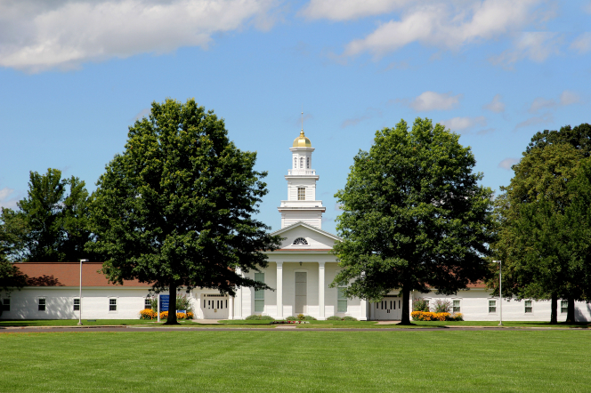 A large grassy lawn and trees in front of a white chapel and visitors' center with a steeple at Peter Whitmer's farm in Fayette, New York.