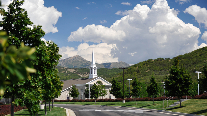 Green, leafy trees and a road leading to a tan chapel with a white steeple and mountains in the background in Draper, Utah.