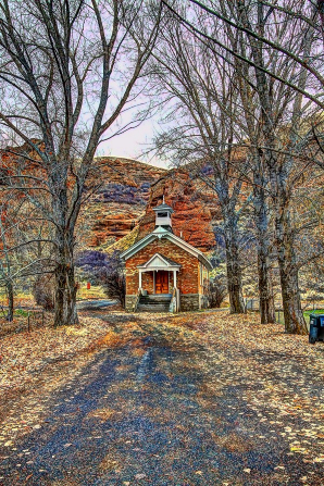 A dirt road bordered by tall trees with leaves on the ground leading to a small chapel in Echo, Utah.