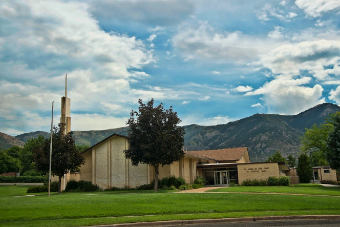 A light brown chapel with a steeple on the side surrounded by a large grass lawn and mountains in the background in Eden, Utah.