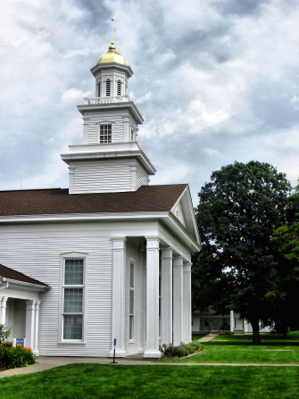 An outside view of the entrance and steeple of a white chapel and visitors' center in Fayette, New York.
