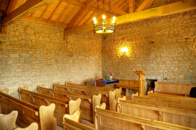 Rows of wooden benches in a chapel with stone walls and a wooden roof in Gadfield Elm, England.