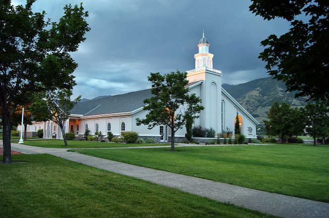 A white chapel at dusk with a steeple and lawn in front with a mountain shown in the background.