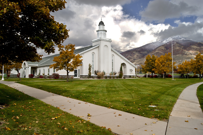 A green lawn, sidewalks, and trees with autumn-colored leaves in front of a white chapel and mountains in the background in Farmington, Utah.