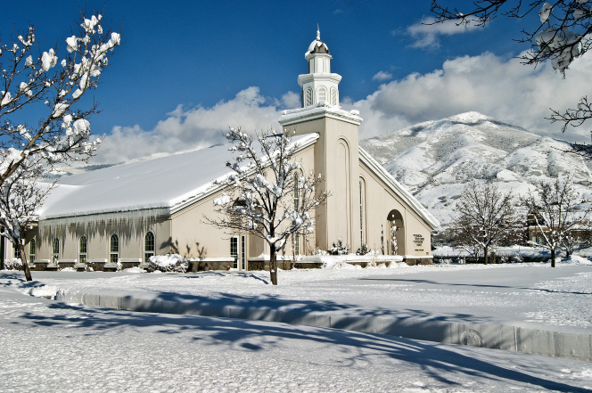 A chapel and surrounding lawn, trees, and mountain covered in snow in Farmington, Utah.