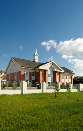 A grass field and white fence in front of a large, red-brick chapel with a steeple and a blue sky with a few clouds overhead in Mongolia.