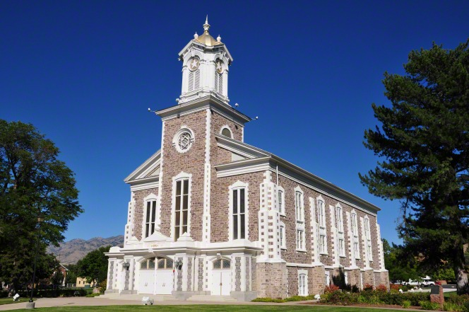 A front view of the Logan Tabernacle consisting of brown bricks, white doors, and a steeple, with trees on each side.
