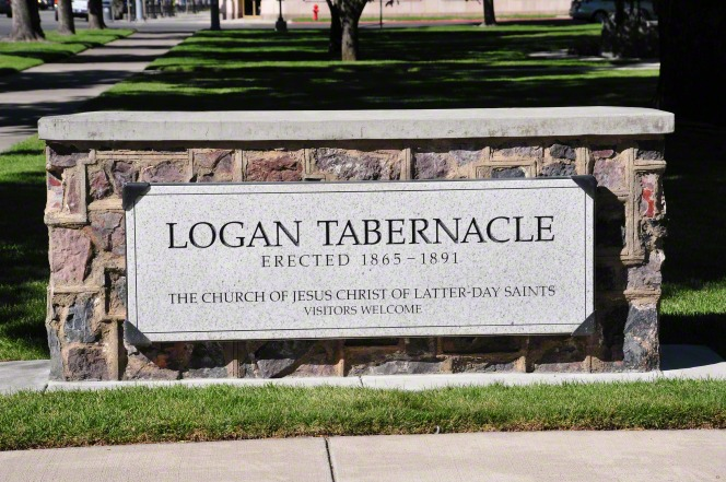 "A sign surrounded by brick that says ""Logan Tabernacle, erected 1865–1891, The Church of Jesus Christ of Latter-day Saints, Visitors Welcome."""