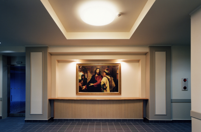 A dimmed meetinghouse foyer with a light shining on a painting of Christ in the center.