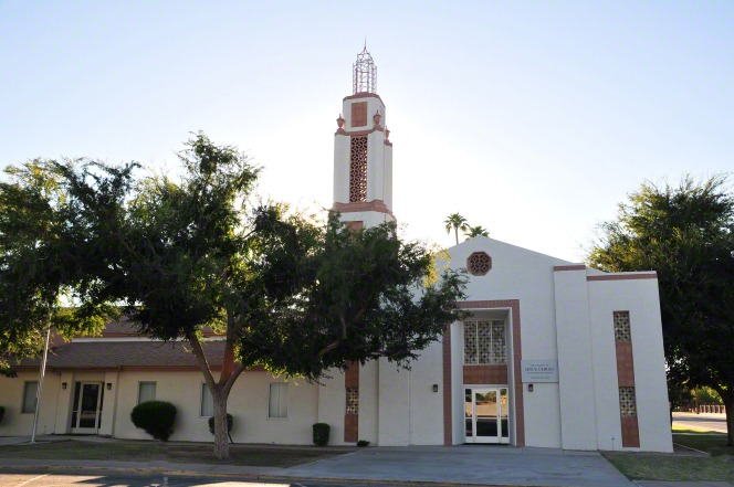 A white chapel in Mesa, Arizona, with a steeple and two glass doors surrounded by grass, trees, and a sidewalk.