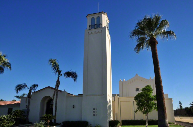 A white chapel in Mesa, Arizona, with a steeple, surrounded by palm trees with a clear blue sky overhead.