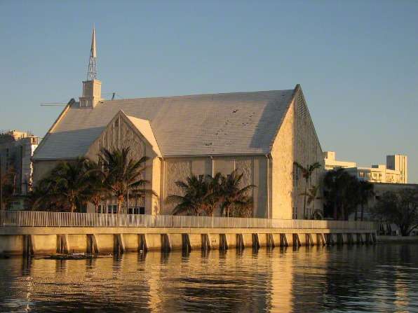 A light brown chapel surrounded by palm trees in Miami, Florida, reflected in nearby water.
