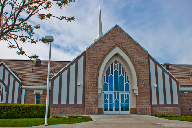 The front view of a brick chapel with stained-glass windows above the entrance doors in Erda, Utah.