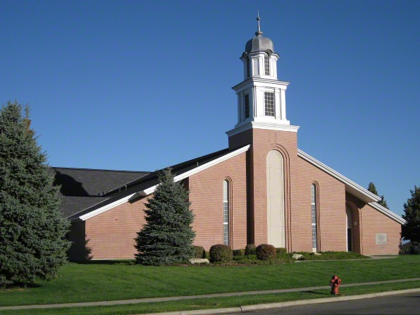 A front view of a brick chapel with a steeple in North Salt Lake, Utah, with grass and pine trees in the front.