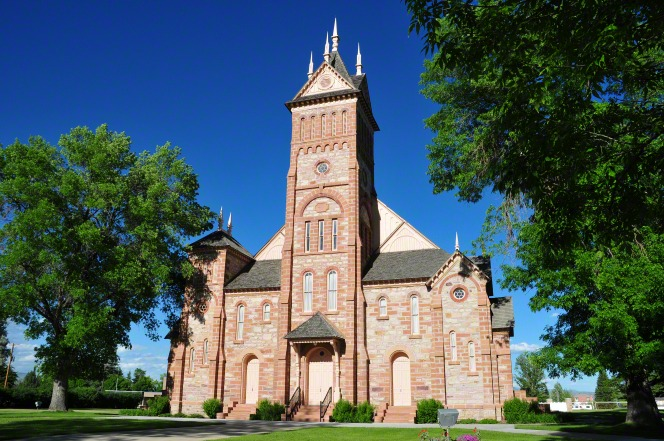 A front view of the historic Bear Lake Stake Tabernacle in Paris, Idaho, consisting of brick in a variety of colors with a large steeple in the front center.