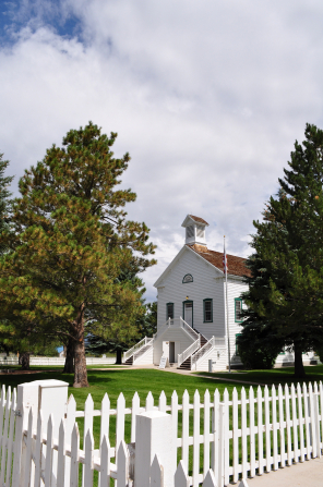 A white wooden fence bordering a lawn, trees, and a historic white chapel in Pine Valley, Utah.
