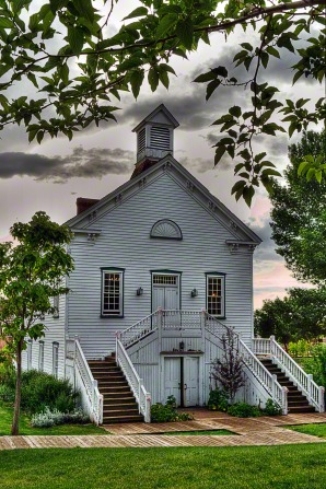 The outside of an old wood chapel painted white with stairs on each side in Pine Valley, Utah.