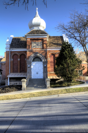 A front view of a small historic chapel made of brick in Salt Lake City, Utah, with white doors and a short, white steeple.