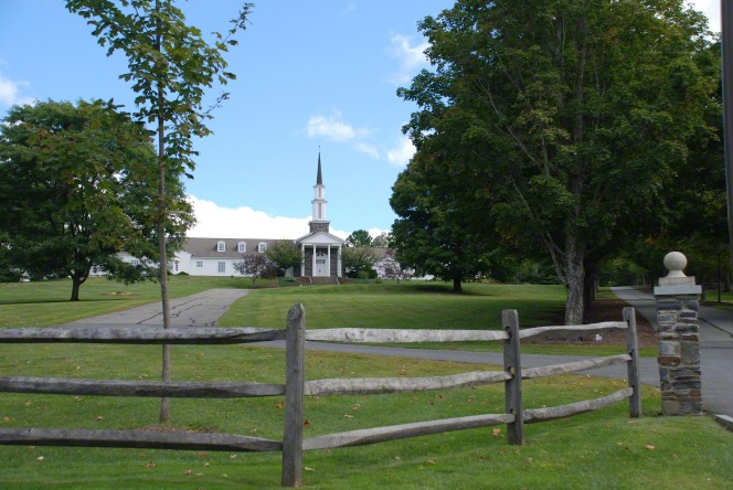 A road leading to a historic meetinghouse in Sharon, Vermont, with trees on each side and a wooden fence in the foreground.