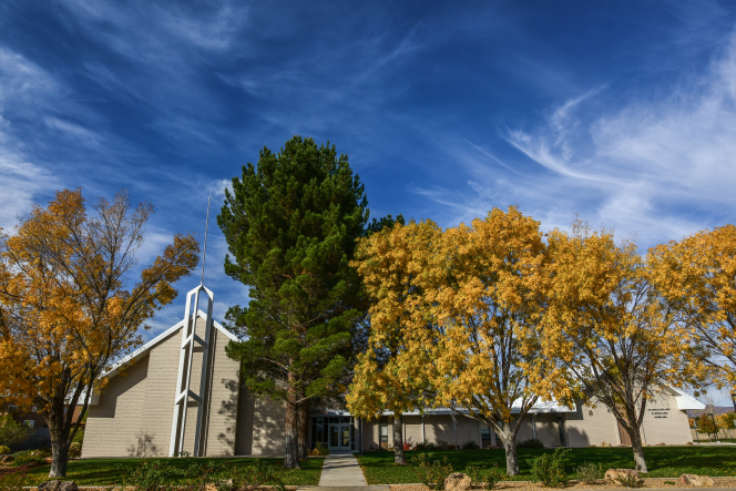 A tan-brick chapel behind trees with yellow, orange, and green leaves and a green lawn in Socorro, New Mexico.