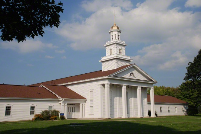 A white chapel and visitors' center with a dark brown roof and a steeple, surrounded by green grass in Fayette, New York.