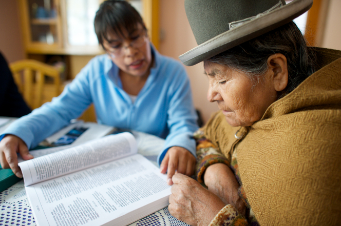 A woman in a blue shirt sitting next to an elderly woman in a brown scarf, who is reading from large scriptures.