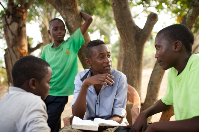 Four young men gather outside by trees and discuss the scriptures together.