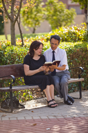 A man in a white shirt, black tie, and gray pants sits on a wooden bench next to a woman in a black dress and sandals as they read the scriptures together.