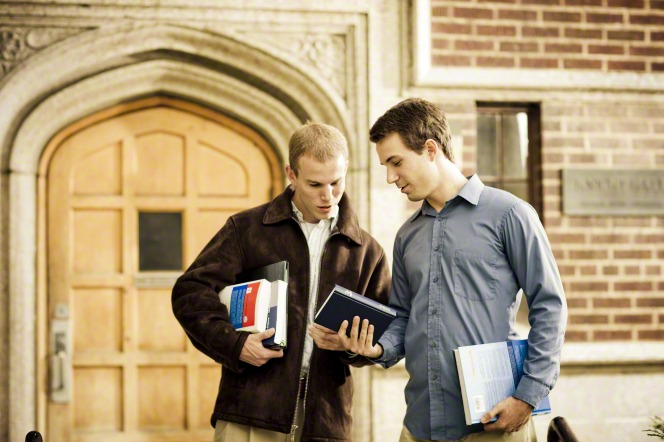 A male college student in a blue shirt standing while looking at the Book of Mormon with another male college student in a brown jacket.