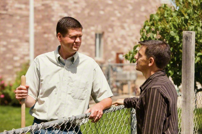 A man with short brown hair standing on a grass lawn and talking to another man in a brown shirt on the opposite side of a metal fence.