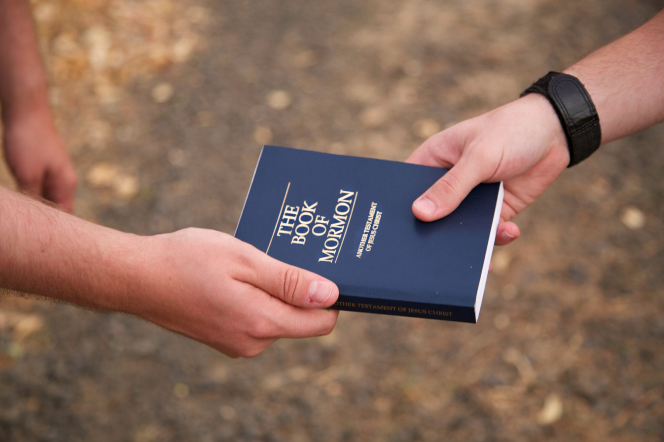 A hand is shown giving a blue paperback Book of Mormon to someone else.