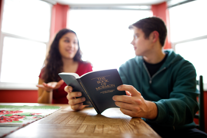 A young woman sits at a table and talks with a young man, who is holding a Book of Mormon open.