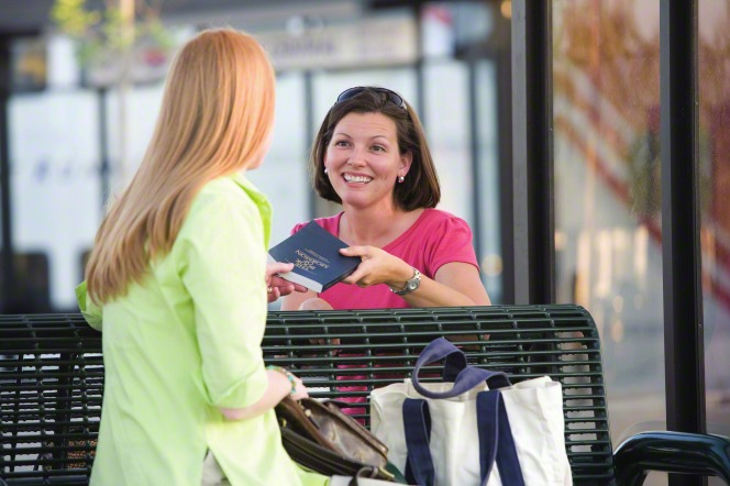 A woman in a pink shirt smiling and handing a Book of Mormon to another woman in a green shirt, who is sitting on a bench outside.