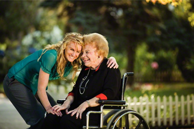 A blonde woman in a blue shirt and gray pants smiles while hugging an elderly woman in a black shirt and pants, who is sitting in a wheelchair outside.